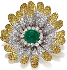 Emerald and diamond brooch, Bulgari, circa 1970.     Designed as a flower, the centre set with a cabochon emerald, the petals set with brilliant-cut diamonds of near colourless and yellow tint, signed Bulgari, case by Bulgari.    Sotheby's.