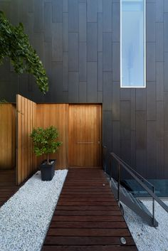 Love this as an idea of the entry - carrying the timber from the door onto the exterior wall.