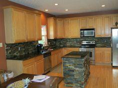 maple kitchen cabinets with dark wood floors, dark countertops