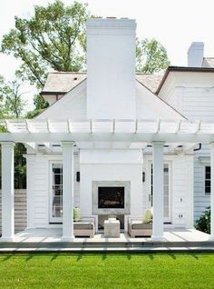 White clapboard home exterior with a freshly painted white pergola and raised deck.