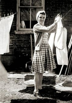 A mid-century housewife hanging up her laundry. This reminds me of my momma & my sisters & I.  This is how we hung our clothes out to dry. #vintage #laundry #homemaker
