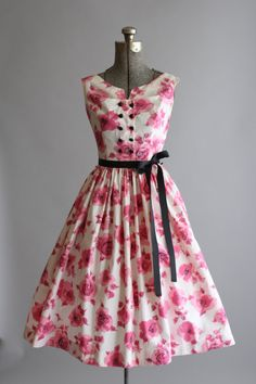 Reserved Reserved Reserved   This Gay Gibson cotton dress features a stylized floral print in shades of pink. Black decorative buttons going down front bodice. Full pleated skirt. Metal zipper up side of dress. Includes a black ribbon waist tie. Very good vintage condition. Please note: two yellow marks on front of skirt, they are pretty hidden in the pleats. There is also a tiny mark on the top left sleeve. Petticoat worn under skirt for added volume. This piece has been cleaned and is…