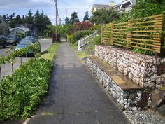 gabion bench. a lovely way to add interest to the street edge of your home. many benefits at once: a retaining wall, shelter and privacy for your front garden, a bench to please pedestrians and using the front verge to grow herbs and salad plants.