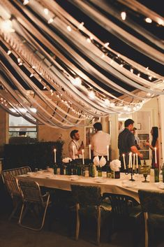 decor featuring a canopy made of lace ribbons and lights, emptied various wine/brown/green bottles, tablecloth from fabric/ and DIY tissue paper flowers// photography by @Sarah Chintomby