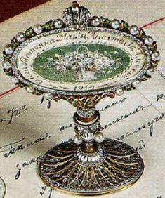 """Names of the children, a basket of flowers and the year """"1914"""" in enamel on the other side. The frame itself is made of pearls and green enamel husks, with an Imperial crown set with rose-cut diamonds on top. The oval base and white enamel vase-shaped pedestal is decorated with diamonds, emeralds and two suspended pearls.  Miss Meadows' Pearls - Fashion, Photography, Alternative Model, Burlesque, Vintage"""