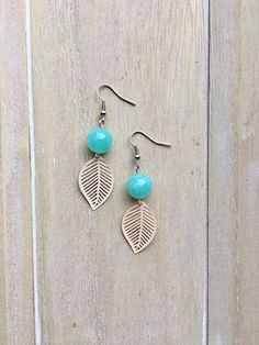 Silver colored dangle earrings with teal bead and salmon pink leaf charm pendant.