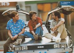 "Robert Zemeckis, Michael J. Fox, and Steven Spielberg have a chat on the hood of the DeLoreon. (""Back to the Future"" set)"