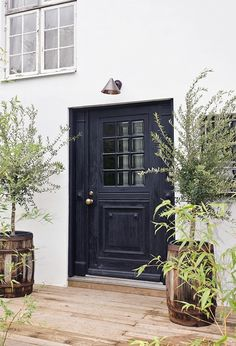 Same size ad our front door....just need to rebalance it...circa lighting + black door + barrel potted trees