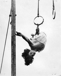 Erma Ward, a turn of the century circus trapeze artist, dangles by one hand from a ring high in a circus tent. Atwell, H.A.