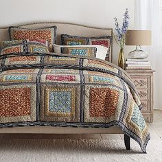 The Sanderson Quilt is a global-chic patchwork of batik-print vines, stylized florals, stripes and tile prints, arranged in a graphic grid.