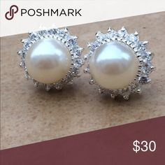 Sterling Silver 925 Statement Pearl CZ Halo Studs Sterling silver 925 round stud earrings feature a faux white pearl at the center with a halo of prong set glittering cubic zirconia surrounding it.  Posts with friction backs attached at the center of the earring.  These statement sized earrings measure 5/8 inch in size.  Perfect for special occasions, bridal, or just to up your chic on a great outfit for work. Jewelry Earrings