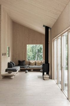 Peek Inside a Minimal Getaway in Sweden | a warm wood interior with wood clad walls, ceiling and floor, a wrap around sofa and black wood burner #nordicinterior #woodcabin #scandinavianstyle