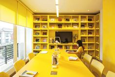 Would you want to work in this colourful office? Vivid, primary colour has been used as a core feature of this design, consisting of three hues — red, blue and yellow — saturating each level. A rainbow-toned, spectrum staircase leads workers from floor to floor, and free hand typographic illustration about design philosophy is drawn onto the surface of the surrounding walls. Yellow Kitchen Interior, Interior Design Yellow, Office Interior Design, Office Interiors, Yellow Office, Yellow Desk, Yellow Walls, Office Color Schemes, Design Commercial