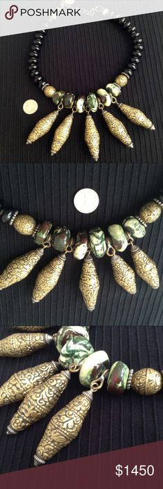 """Spectacular Masha Archer Statement Necklace Large, exotic,  necklace by the remarkable designer Masha Archer. EUC. Black resin beads lead into gold toned hand carved brass beads, followed by some kind of marbled jasper in swirling green & cream, crowned by 5 tremendous bicone beads with carved floral & animal motif. Even the spacers and caps are unique tribal silver beads. Masha sources her materials from antique troves spanning the globe. 19"""" long adjustable to 23"""", 289g. Bold & expressive…"""