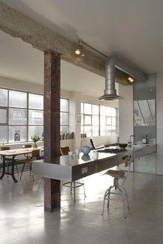 The London loft of Ochre partner Solange de la Fouchardière features polished concrete floors, exposed ventilation ducts, and a glass backsplash.