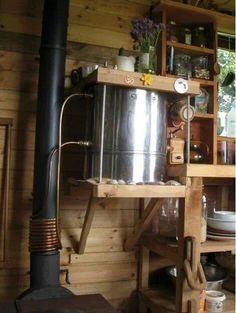Hot water tank heated by wood burning stove. From Teach Nollaig, Tiny house in Ireland. Could be improved by adding a small sterling engine to power a circulation pump, allowing the hot water tank to be up higher [improving pressure]. Also INSULATION! Off The Grid, Wood Stove Water Heater, Diy Wood Stove, Solar Water Heater, Tiny House Wood Stove, Stove Heater, Rocket Stoves, Water Heating, Tiny House On Wheels