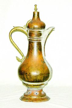 This is an ancient copper coffee pot with brass handle, hinge and top finial.  It has spent many years warming in the embers of a Bedouin ca...