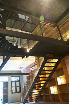House N° 17 - Stepping in, a linear reflective pond delineates a formal entrance foyer, which one crosses via granite slabs into the house proper. A metal platform bridge with industrial mesh balustrades runs the length of the house. Alongside the bridge is a double storey height wooden bookshelf set against the shophouse wall, appealing to the fantasy of having your own library, while the island open-plan kitchen is ideal for lazy breakfasts.