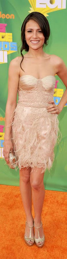 Italia Ricci wears a nude bustier dress with feathered skirt and gold sandals.