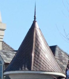 copper turret roof with custom diamond shaped copper roof tile and a copper finial roof cap - closeup picture
