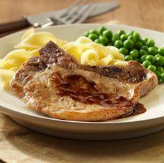 Chuletas de cerdo con hueso cortadas finas, de cocción rápida en sartén y rociadas con salsa tibia de miel y mostaza