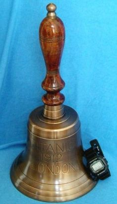 "HMS Titanic Brass Hand Bells. Beautifully finished to look aged. Great Handbell and Titanic momento centerpiece. This is a HUGE and beautiful handle bell, that rings loud with 3/16"" thick solid brass. The clapper alone is 4-1/2 inches long and 1 inch wide at its end. Bell has nice lines and shape. Three incised lines as it flares out, and a 7 inch wooden handle, with a brass escutcheon on top. Overall measurements are 16 inches tall x 8 inches …"