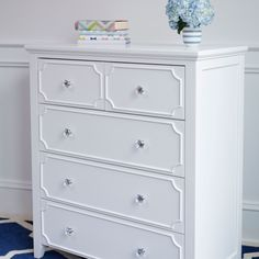 White tall, 2 over 3 drawer dresser with crystal knobs and detailed drawer fronts. Polished and pretty, white goes with everything!