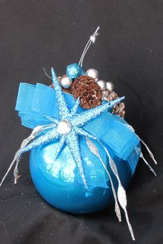 Christmas ornament decorated with pine cones and miniature ornaments