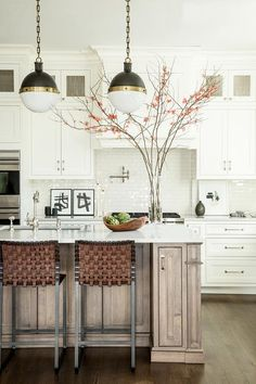Three Small Hicks Pendants illuminates a walnut stained kitchen island topped with white quartz fitted with a dark steel sink and a vintage faucet kit lined with leather basketweave counter stools.