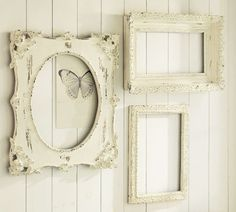 empty frames on a beadboard-type wall. Love the butterfly ephemera behind the oval frame.