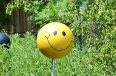 """Discarded Bowling Ball gets a new look at life as """"SMILEY FACE"""" in the Linneman House Landscaping"""