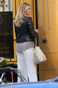Stylish: The model wore a pair of white trousers, a grey blouse with a cropped leather jac...
