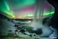 Northern lights in Iceland from behind Seljalandsfoss Waterfall