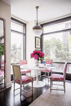 Dining area with Hicks pendant by Thomas O'Brien, Saarinen tulip table, pink damask fabric, pink hydrangeas. Via Domino.