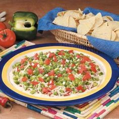 """Layered Creamy Taco Dip Recipe -Layered in a pizza pan, this taco dip makes a pretty presentation! """"I prepared this yummy spread for birthday parties and family get-together,"""" says Janet Vrieselaar of Rosedale, British Columbia. """"It's wonderful spread on baked tortilla chips or low-fat crackers. I never seem to make enough—it's always the first appetizer to go."""""""