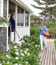 Linda greets her daughter Lily from the cottage's new screened front porch, underplanted with Rosa rugosa.   - CountryLiving.com
