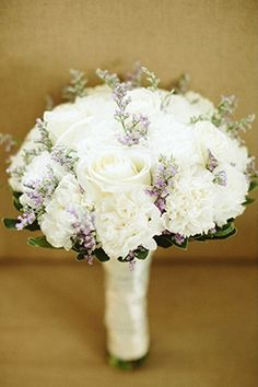A hint of lavender hues in an all-white wedding bouquet of roses and carnations. | From Angel & Pawee's wedding, as featured on www.bridalbook.ph