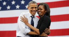 Former President Barack Obama and former First Lady Michelle Obama embrace onstage during a campaign event at the University of Iowa in