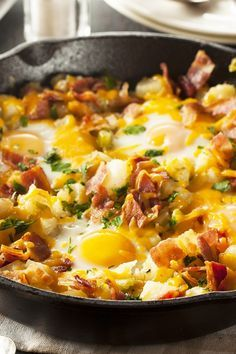 Recipe including course(s): Entrée; and ingredients: bacon, black pepper, cheddar cheese, egg, green bell pepper, mushrooms, onion, potatoes, red bell pepper, salt