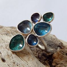 Handmade sterling silver ring decorated with shades of blue enamel and resin circles.