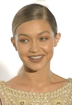 Gigi Hadid with a sleek low pony tail - use tail-comb to create side-parting above arch of eyebrow, then scoop hair into sleek, ponytail