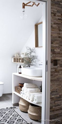 White rustic bathroom, wicker basket storage, botanical.