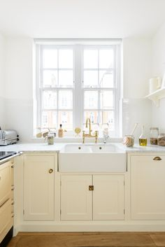 The double sink looks out onto a courtyard and the big sash window floods the room with so much light, the reflections from the Carrara Marble worktops and the Brass fittings add to the instant feeling of quality in this room