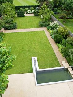 This orderly garden combines neatly-edged lawn with lush perennials and shrubs planted on the margins for visual contrast.