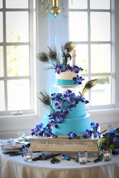 Beautiful peacock & orchid wedding cake; I'm obsessed with these flowers...would not put feathers on my cake though
