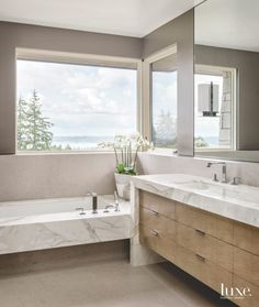 With marble features and panoramic views, this contemporary bathroom is full of high design.