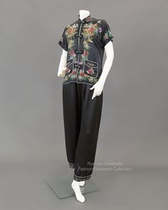 Black silk lounging pajamas with multi-coloured embroidery of flowers and birds. Mandarin collar, piped pocket detail, frog closures, piped short sleeves and hem. Matching pants, c.1930. FRC2013.03.002A+B