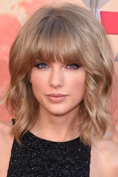 Blunt bangs aren't for everyone, but Swift pulls off the style with ease.   - ELLE.com