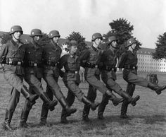 Practicing goose stepping: Dutch volunteers of the Westland Waffen SS regiment; the short German NCO in the middle sets the silent cadence. Learning how to goose step was done with hands clasped behind the back in order to test the balance of the learner.