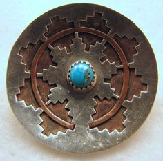 A beautiful work of art by Navajo artisan Betty Platero ..    Beautiful Native American woven basket motif brooch with a traditional design ... the Navajo Wedding Basket is viewed as a map through which the Navajo chart their lives ... so much history and tradition ... this beautiful brooch is a combination of copper and sterling silver ... sterling silver hand-cut to show the copper level below ... a small nugget of genuine turquoise with beautiful color and natural matrix sits bezel set in…